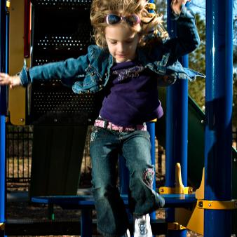 Young girl jumping off a climbing gym at a playground